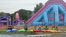 Paddlers wait for a thunderstorm to pass beneath a dormant bouncy castle