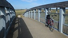 The bicycle, fixed after 9 years' dormancy, gets its first ride across the Reach Lode bridge